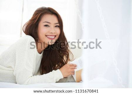 Portrait of beautiful cheerful woman with a book #1131670841