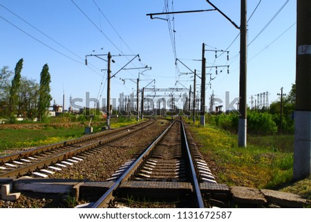 Rail road on country side in summer with a lot of electric poles on it sides #1131672587