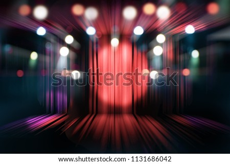 blurred theater stage with red curtains and spotlights, abstract image of concert lighting Royalty-Free Stock Photo #1131686042