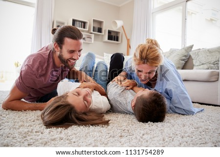 Parents Tickling Children As They Play Game In Lounge Together #1131754289