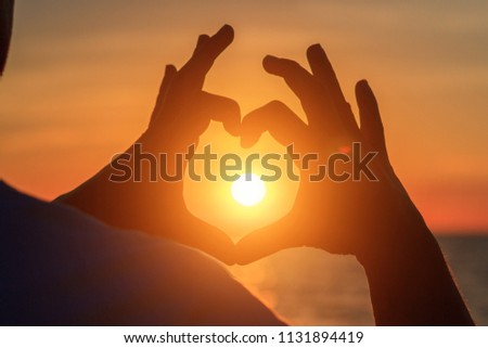 men's hands in the form of heart against sunlight in sunset sky, twilight time. Hands in shape of love heart, Love concept. #1131894419