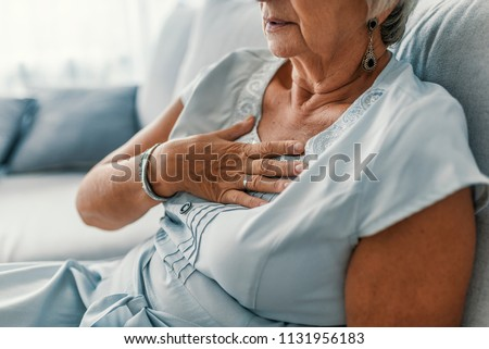 Woman having a pain in the heart area. Heart Attack. Painful Chest. Health Care, Medical Concept. High Resolution. Woman having heart attack at home #1131956183