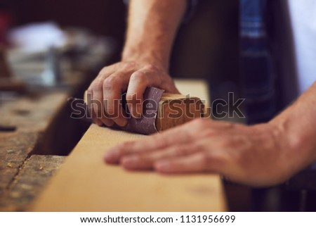 Close-up of carpenter using sandpaper on a wooden plank in a carpentry shop #1131956699
