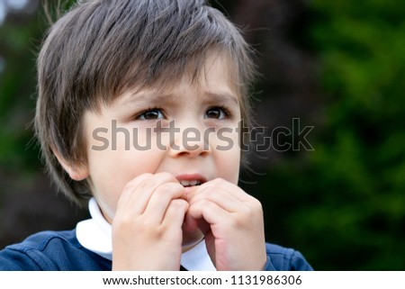 Portrait of toddler boy biting his finger nails while looking at some thing at the park, Childhood and family concept, emotional child portrait #1131986306
