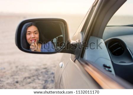 Female driver applying lipstick using rear mirror in a car #1132011170