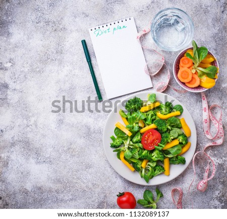 Diet plan. Healthy vegetable salad, clean water and measuring tape. Top view #1132089137
