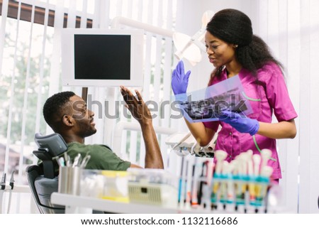Dentisry concept, healthcare, oral and teeth care. Happy young beautiful african woman dentist holding the teeth x-ray and speaking with the patient #1132116686