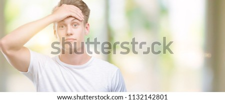 Young handsome blond man stressed with hand on head, shocked with shame and surprise face, angry and frustrated. Fear and upset for mistake. #1132142801