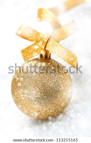 Glittering gold Christmas ball with an ornamental gold bow in winter snow with falling snowflakes