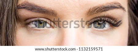 Beauty and fashion concept - Eyelash Extension Procedure. Before and after. Woman Eyes with Long false Eyelashes. Close up macro shot Royalty-Free Stock Photo #1132159571