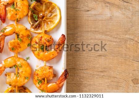 Grilled tiger shrimps skewers with lemon - seafood style #1132329011
