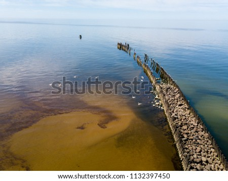 Old wood and rocks breakwater #1132397450