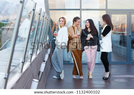 Four young charming women classmates celebrating ten years after graduation with glasses of wine on the open roof of a beautiful and expensive modern restaurant #1132400102