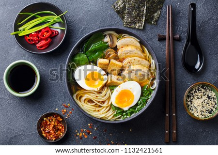 Asian noodle soup, ramen with chicken, tofu, vegetables and egg in black bowl. Slate background. Top view. #1132421561