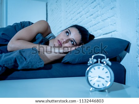 young beautiful hispanic woman at home bedroom lying in bed late at night trying to sleep suffering insomnia sleeping disorder or scared on nightmares looking sad worried in mental health concept #1132446803