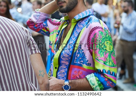 MILAN - JUNE 16: Man with colorful Versace shirt with green Medusa head before Versace fashion show, Milan Fashion Week street style on June 16, 2018 in Milan. #1132490642