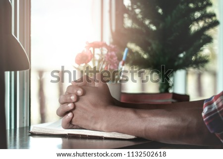 Close up hands man praying on holy Bible at home. #1132502618
