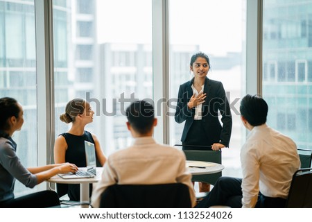 A young Indian Asian woman stands up in front of her diverse team and is leading a meeting, training or presentation in their office during the daytime. They are an ethnically diverse team. #1132524026