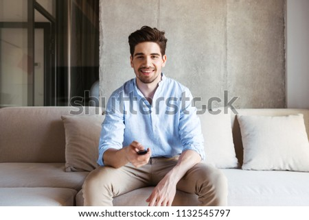 Smiling young man holding TV remote while sitting on a couch at home #1132545797