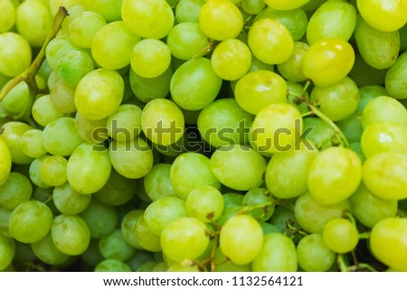 Green fresh grapes bunch lies in a wicker basket in the counter of a small market. Ingredients and light snacks. Juicy fresh harvest from the farm. Soft focus and beautiful bokeh. #1132564121