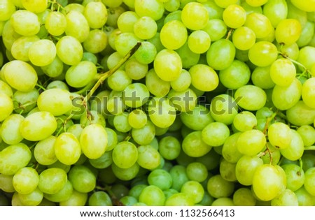 Green fresh grapes bunch lies in a wicker basket in the counter of a small market. Ingredients and light snacks. Juicy fresh harvest from the farm. Soft focus and beautiful bokeh. #1132566413