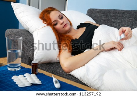 Young sick woman lying in bed holding pills #113257192