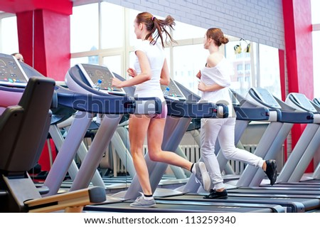 Two young sporty women run on machine in the gym centre #113259340