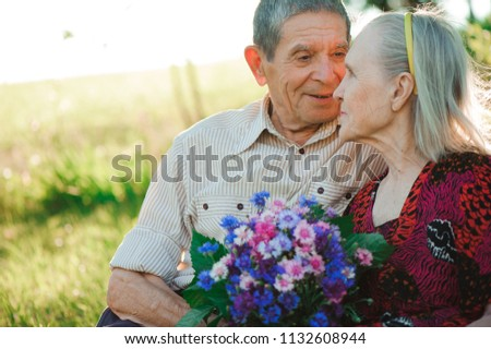 beautiful happy old people sitting in the  park #1132608944