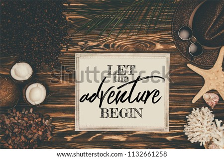 """top view of vintage map  surrounded with various tropical travel attributes on wooden surface with """"let the adventure begin"""" inspection  #1132661258"""