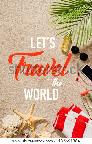 top view of striped towel with various objects lying on sandy beach, lets travel world inscription #1132661384