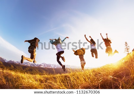 Group of five happy friends runs and jumps against mountains at sunset time. Travel or expeditions concept #1132670306