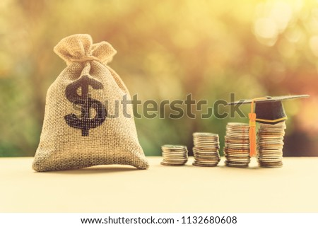 Money cost saving for goal and success in school, education concept : US dollar / cash in hemp bags or burlap sacks, a graduation cap or hat on highest row of coins, depicts final study or achievement #1132680608