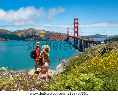 Couple looking at beautiful summer coastal landscape, on hiking trip. Friends  relaxing on mountain. Golden Gate Bridge, over Pacific Ocean and San Francisco Bay, San Francisco, California, USA. #1132707851