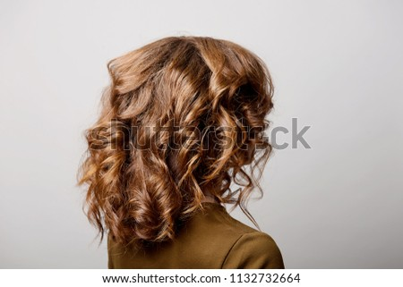 Female hairstyle long curls on the head of the brown-haired woman back view at the gray background turning the head to the right. #1132732664