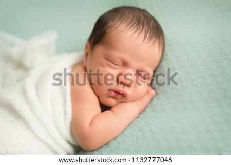 newborn photoshoot portrait palm under the cheek on mint knitted backdrop