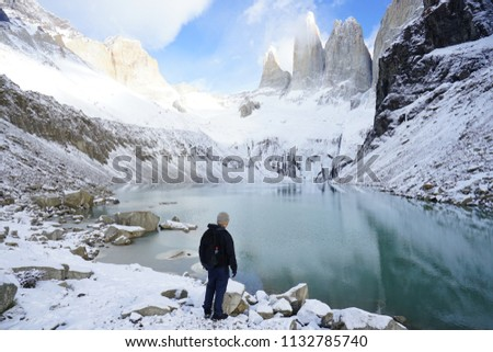 The Asian male traveller standing at the base of Torres del Paine in winter with the background of snow covered mountains and reflection in water at Torres del Paine national park, patagonia in Chile #1132785740