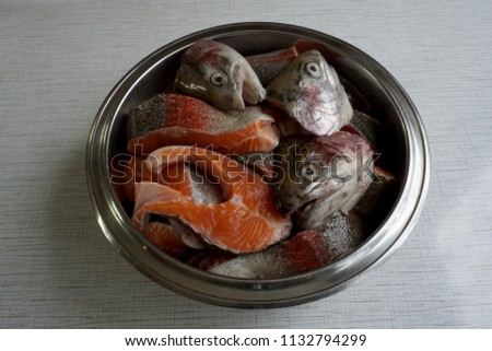 Many pieces of raw red fish and three heads lie in a metal bowl standing on the table. #1132794299