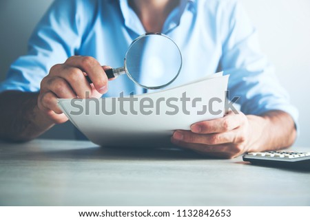 Businessman looking through a magnifying glass to documents #1132842653