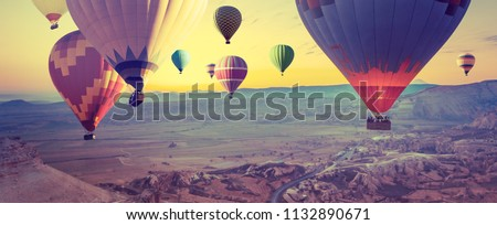 Panorama of Cappadocia at sunrise - multicolored hot air balloons above mountain. Wide landscape of Goreme valley in Turkey - your travel concept in retro style with effect of instagram filters. #1132890671