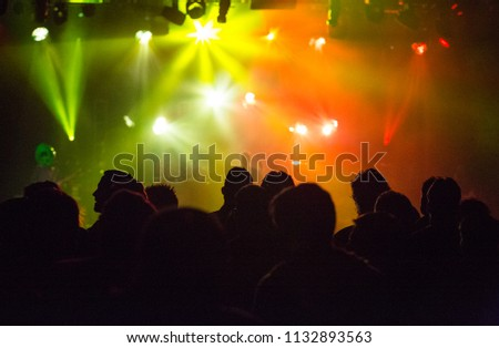 Green and orange lights at concert with crowd silhouette #1132893563