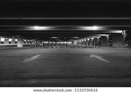 Empty parking garage with overhead lights and an exit sign hanging from the ceiling in black and white. #1132930616