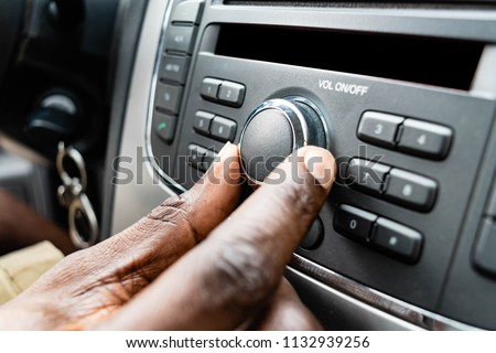 African American male turning on car air conditioning system, finger hitting car emergency light button, Black man's Hand tuning fm radio button in car audio system. transportation and vehicle concept #1132939256