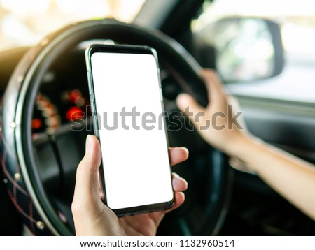 Driver holding smartphone in hand, use smart phone while driving. Isolated white screen for mock up, graphic design or app promotion. Steering wheel interior right-hand drive car in background.