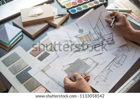 Architect designer Interior creative working hand drawing sketch plan blue print selection material color samples art tools Design Studio #1133058542