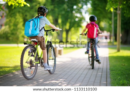 Children with rucksacks riding on bikes in the park near school. Pupils with backpacks outdoors Royalty-Free Stock Photo #1133110100