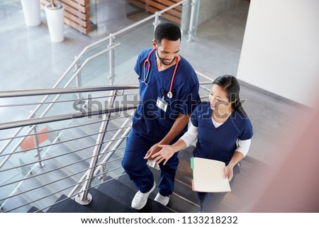 Two healthcare colleagues talking on the stairs at hospital #1133218232