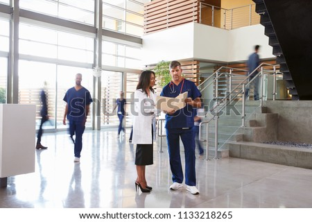 Two healthcare workers talk in the lobby of a busy hospital #1133218265