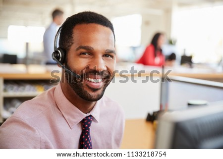 Man working in a call centre smiling to camera, close-up #1133218754