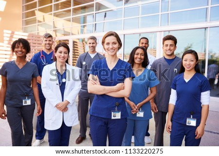 Team of healthcare workers with ID badges outside hospital Royalty-Free Stock Photo #1133220275