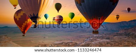 Many colorful hot air balloons flight above mountains - panorama of Cappadocia at sunrise. Wide landscape of Goreme valley in Cappadocia -  billboard background for your travel concept in Turkey. #1133246474